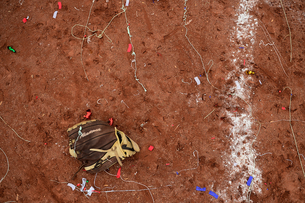 . A Legacy\'s player\'s glove sits among silly string and confetti following the Lightning\'s 6-4 state title win over Legend at the Aurora Sports Park on Sunday, October 20, 2013. The win was Legacy\'s sixth title in seven years. (Photo by AAron Ontiveroz/The Denver Post)