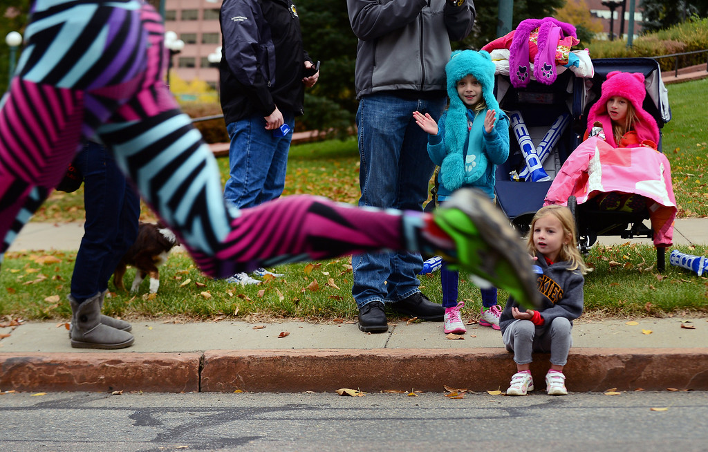 . Makenna Witkiewicz, 3 seated on the  sidewalk, and her sisters  Maya, 5, in blue and Megan, 6 in pink, watch runners as they fly by during  the 4th annual Rock \'N\' Roll Marathon and 1/2 Marathon sponsored by Sports Authority in Denver, Co on October 20, 2013.  More than 15,000 participants and thousands of spectators, family and friends took part in the festivities that started and ended in Civic Center park. (Photo By Helen H. Richardson/ The Denver Post)