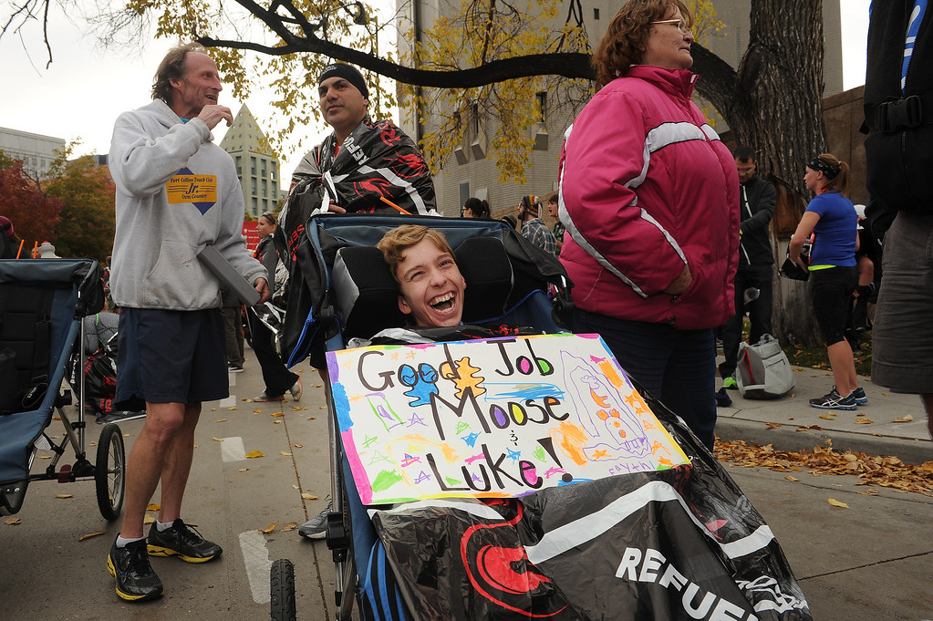 """. Luke Olmstead smiles after completing the half marathon with friend and Lakewood police officer Jesus \""""Moose\"""" Chavez, in back in middle, in Denver, Co on October 20, 2013.   Chavez  Olmstead, who suffers from cerebral palsy, the entire length of the race in Denver, Co on October 20, 2013.  The two took part  in the 4th annual Rock \'N\' Roll Marathon and 1/2 Marathon.  More than 15,000 participants and thousands of spectators, family and friends took part in the festivities that started and ended in Civic Center park. Chavez is a school resource officer for Alameda High School as well as a detective with Lakewood Police Department.  He goes above and beyond the call of duty trying to help students in need.    Olmsted, a sophomore at Alameda High School, has cerebral palsy and can not walk.  Chavez and Olmsted finished the race in just over two hours. (Photo By Helen H. Richardson/ The Denver Post)"""