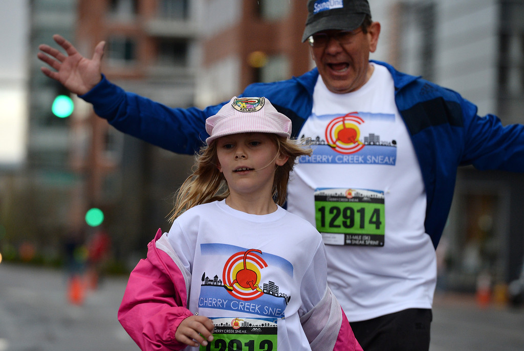 . John Kozlevchar cheers on his daughter Annie, 8, as the two cross the finish line of the 5k race. (Photo By Helen H. Richardson/ The Denver Post)