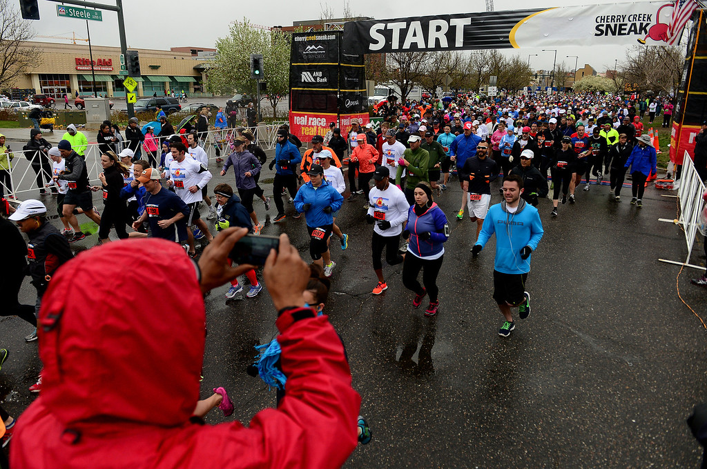 """. Runners participating in the 32nd annual Cherry Creek Sneak in Denver sprint across the starting line of the 5-mile run of the 32nd annual Cherry Creek Sneak in Denver on April 27, 2014. The \""""Sneak\"""" included a 10-mile, a 5k and a 5-mile race. All the races started and finished along East 1st Ave in Cherry Creek. (Photo By Helen H. Richardson/ The Denver Post)"""