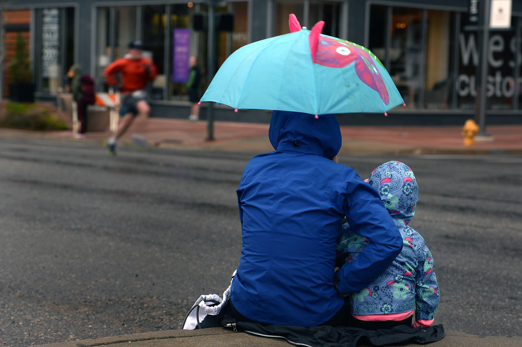 . Ali Metzl and her daughter Anna, keep dry under an umbrella as they watch runners participating in the 32nd annual Cherry Creek Sneak.  (Photo By Helen H. Richardson/ The Denver Post)