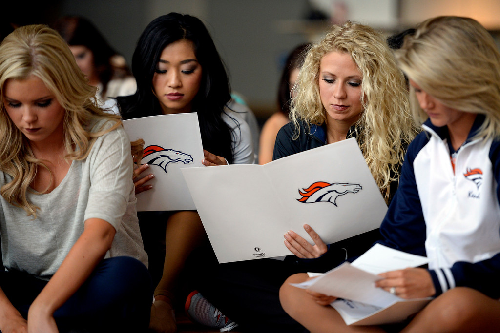 . Toni Gabrilli (right center) and Kisato Nishimura read their packets of team information during tryouts for the 2014-2015 Denver Broncos cheerleaders. More than 100 women showed up and 57 finalists were selected for the 26 spots on the team at Sports Authority Field at Mile High on Sunday, March 30. (Photo By AAron Ontiveroz/The Denver Post)