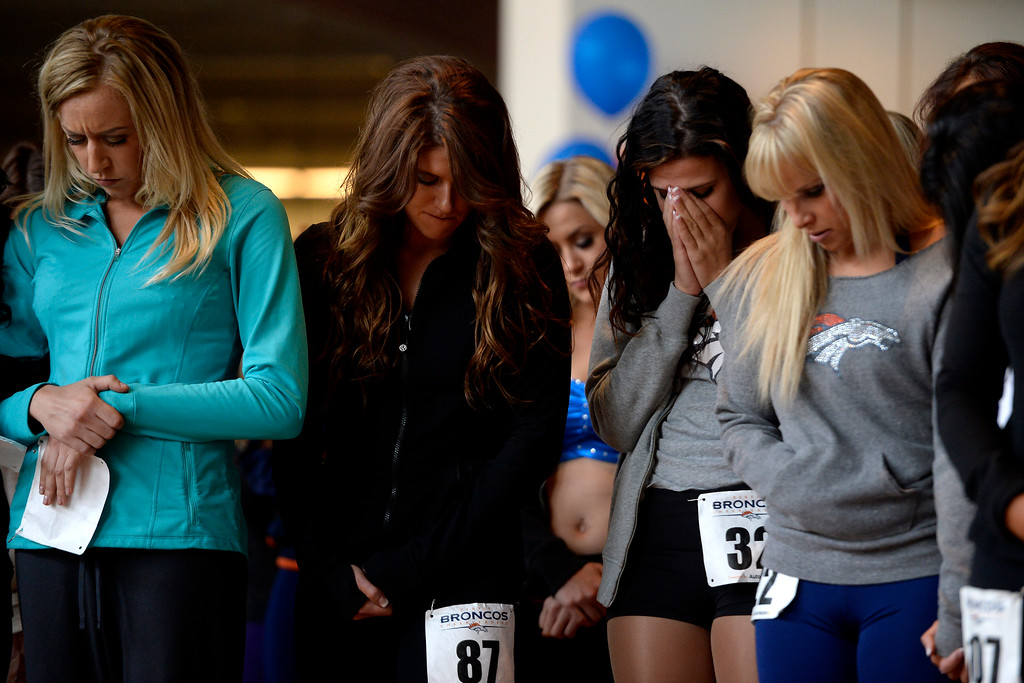 . Women bow their heads as they wait to hear their numbers called during tryouts for the 2014-2015 Denver Broncos cheerleaders. More than 100 women showed up and 57 finalists were selected for the 26 spots on the team at Sports Authority Field at Mile High on Sunday, March 30. (Photo By AAron Ontiveroz/The Denver Post)