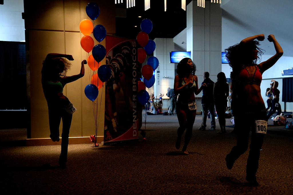 . From left to right Emily Maginnis, Kisato Nishimura and Patricia Reimann warm up during tryouts for the 2014-2015 Denver Broncos cheerleaders. More than 100 women showed up and 57 finalists were selected for the 26 spots on the team at Sports Authority Field at Mile High on Sunday, March 30. (Photo By AAron Ontiveroz/The Denver Post)