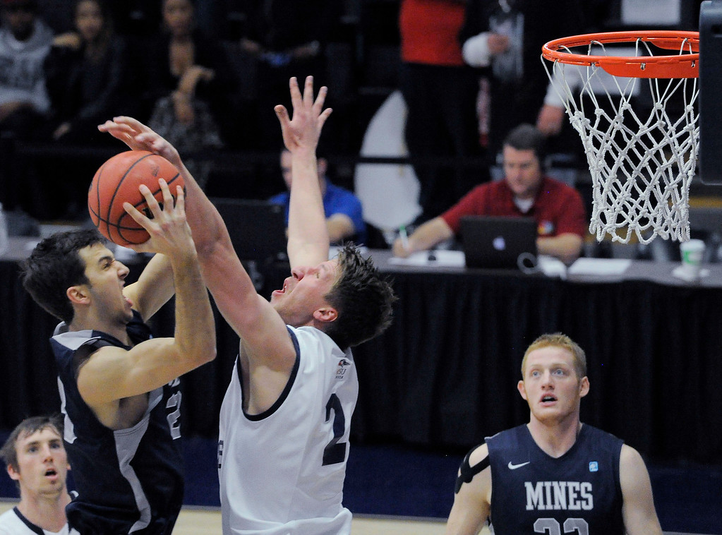 . Metro State\'s Will Sinclair (2) blocks a shot by Colorado Mines\' Caleb Waitsman (23) during the first half of the Division ll Men\'s Basketball Championship Tournament March 16, 2014 at Auraria Event Center (Photo by John Leyba/The Denver Post)