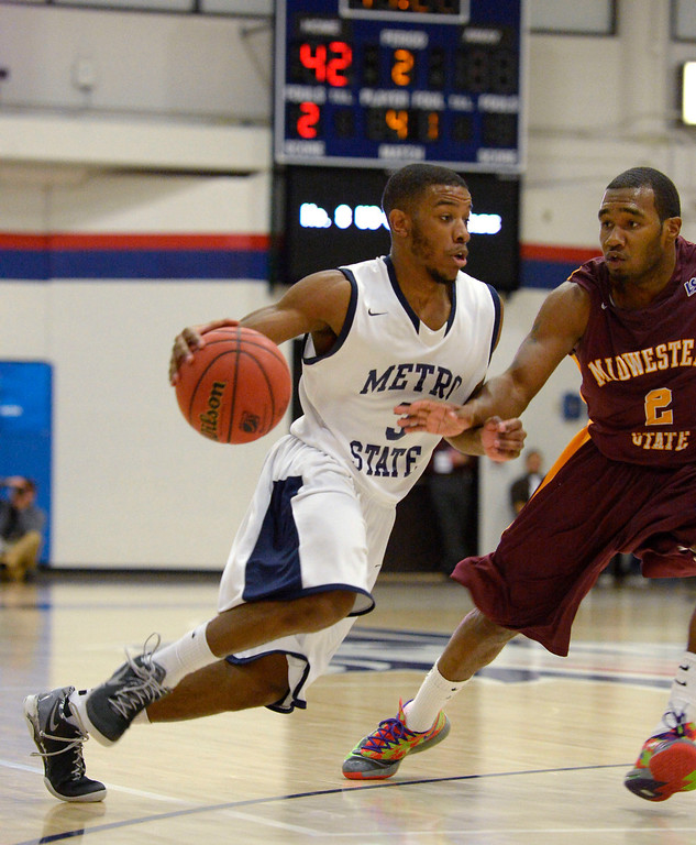 . Metro State Brandon Jefferson (3) drives on Midwestern State DeJuan Plummer (2) during the second half March 18, 2014 in the Championship game of the Division ll Men\'s Basketball Championship at Auraria Events Center. (Photo by John Leyba/The Denver Post)