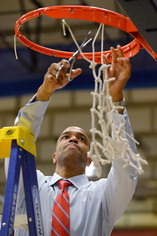 . Metro State head coach Derrick Clark cuts down the net after their victory over Midwestern State 78-56 March 18, 2014 in the Championship game of the Division ll Men\'s Basketball Championship at Auraria Events Center. (Photo by John Leyba/The Denver Post)