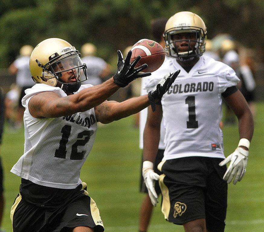 . BOULDER, CO. - AUGUST 06: Wide receiver Keenan Canty (12) snagged a pass in front of teammate Elijah Dunston (1) Tuesday. The University of Colorado football team practiced for the first time Tuesday afternoon, August 6, 2013. Photo By Karl Gehring/The Denver Post