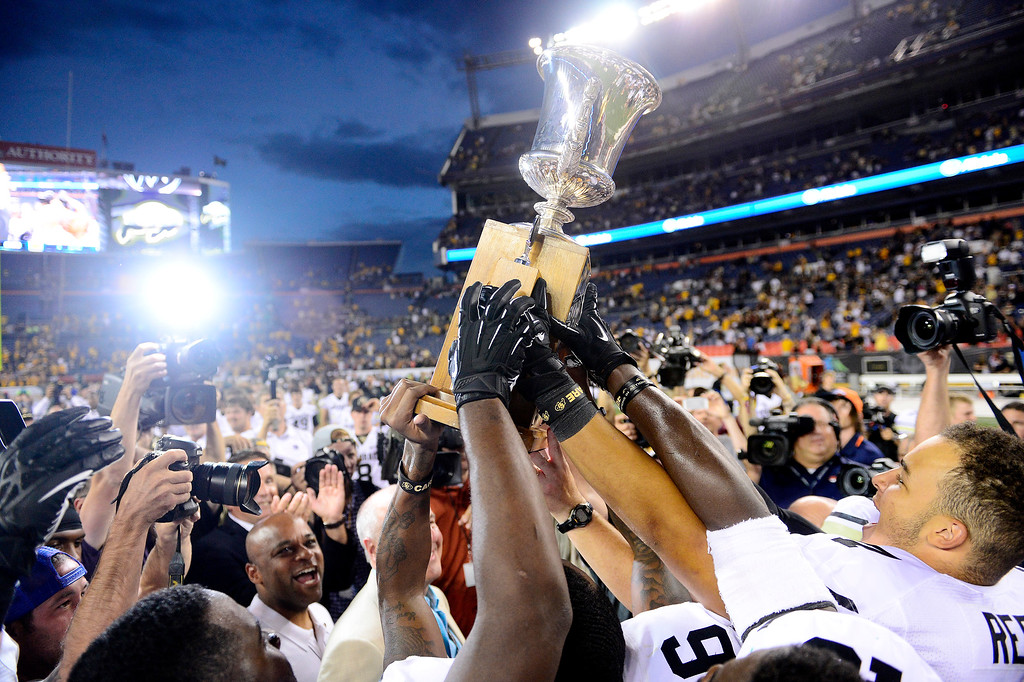 . Colorado Buffaloes players hoist the Centennial Cup following the second half of the Buffaloes\' 41-27 Rocky Mountain Showdown win over the Colorado State Rams at Sports Authority Field at Mile High on Sunday, September 1, 2013. CU leads the all-time series. (Photo by AAron Ontiveroz/The Denver Post)