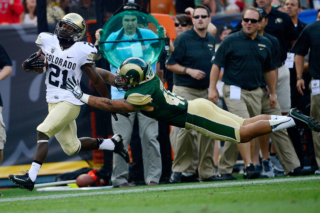 . Nu\'uvali Fa\'apito (45) of the Colorado State Rams extends to force D.D. Goodson (21) of the Colorado Buffaloes out of bounds during the first half of the Rocky Mountain Showdown at Sports Authority Field at Mile High on Sunday, September 1, 2013. CU leads the all-time series. (Photo by AAron Ontiveroz/The Denver Post)