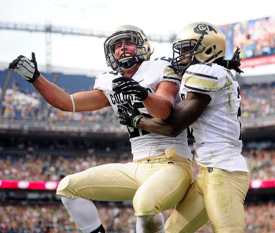 . D.D. Goodson (21) of the Colorado Buffaloes celebrates his touchdown grab against the Colorado State Rams with teammate Nelson Spruce (22) of the Colorado Buffaloes during the first half of the Rocky Mountain Showdown at Sports Authority Field at Mile High on Sunday, September 1, 2013. CU leads the all-time series. (Photo by AAron Ontiveroz/The Denver Post)