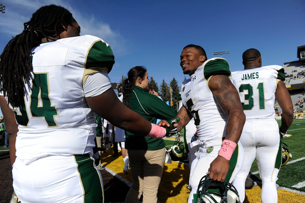 . Colorado State RB, Kapri Bibbs, right, celebrates with teammate, LaRyan King, left, on the bench with just a few minutes left on the clock during the game against Wyoming at Jonah Field at War Memorial Stadium Saturday, October 19, 2013. The Rams won 52-22. (Photo By Andy Cross/The Denver Post)