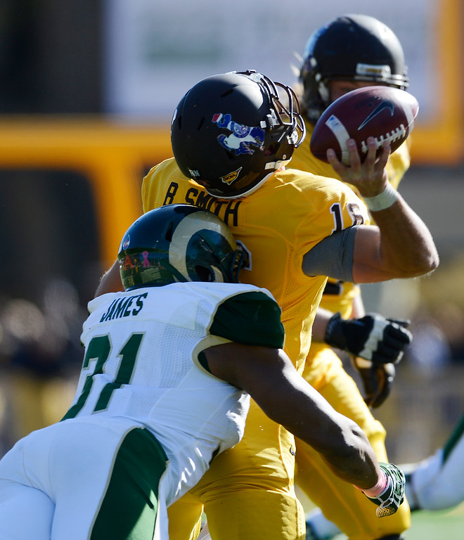. Colorado State LB, Cory James, clobbers Wyoming QB, Brett Smith on a pass attempt in the fourth quarter of play at Jonah Field at War Memorial Stadium Saturday, October 19, 2013. The play was ruled an incomplete pass. Rams won 52-22. (Photo By Andy Cross/The Denver Post)