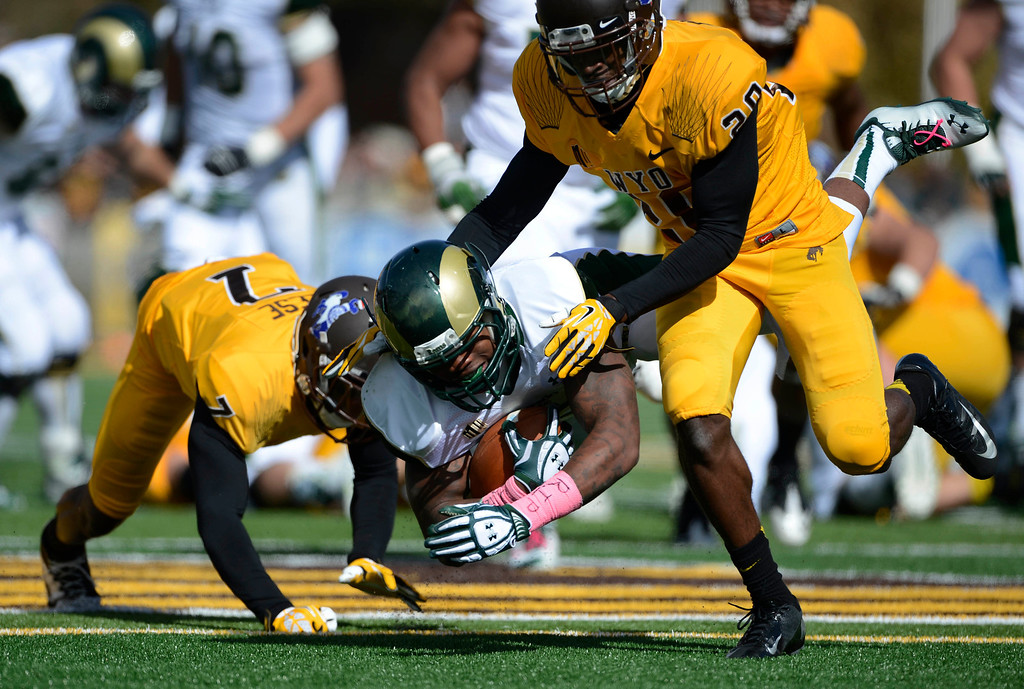. Colorado State University RB, Kapri Bibbs, center, gets wrapped up by Wyoming defenders, Chad Reese, left, and Nehemie Kankolongo, right, after a long gain in the first quarter of play at Jonah Field at War Memorial Stadium Saturday, October 19, 2013.  (Photo By Andy Cross/The Denver Post)