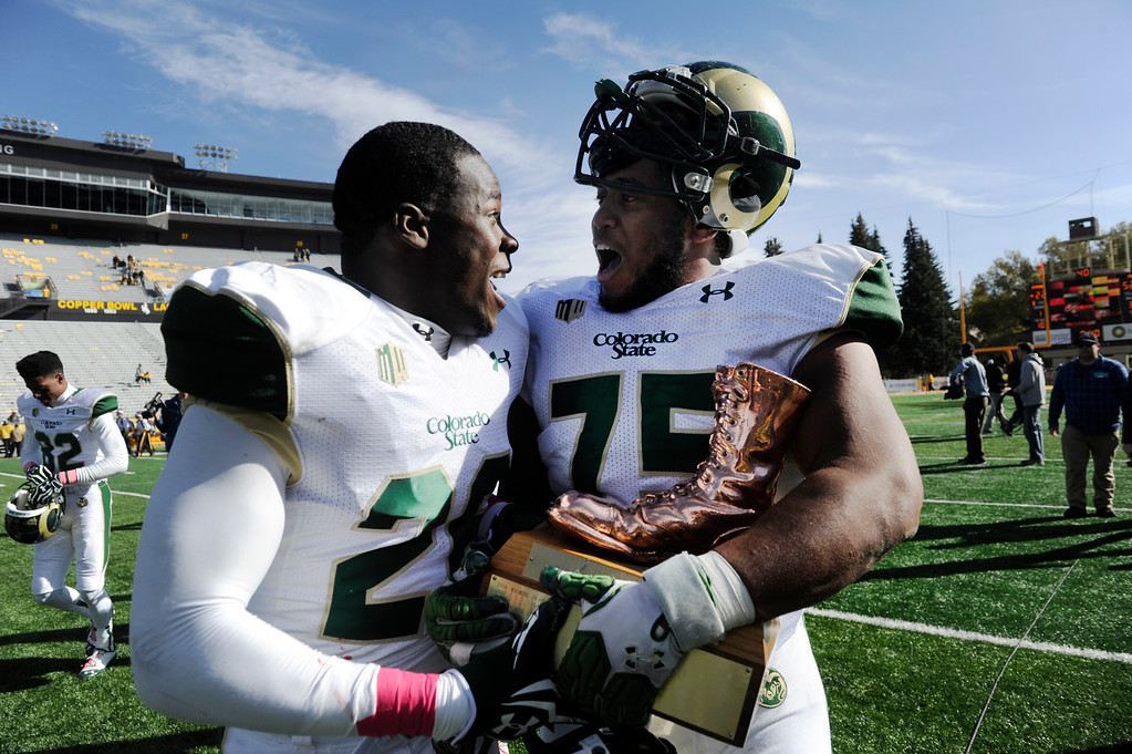 . Colorado State football players, Kevin Pierre-Lewis, left, and Brandon Haynes, right, try to decide who gets to carry the �bronze boot� in celebration after defeating the Wyoming Cowboys, 52-22 War Memorial Stadium Saturday, October 19, 2013. The winner of the annual game between the two teams gets to take the boot. (Photo By Andy Cross/The Denver Post)