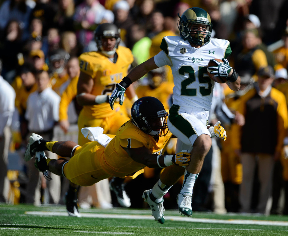. CSU WR, Joe Hansley, gains good yardage on the first play of the game despite tackle effort by Jordan Stanton, Wyoming at Jonah Field at War Memorial Stadium Saturday, October 19, 2013.  (Photo By Andy Cross/The Denver Post)