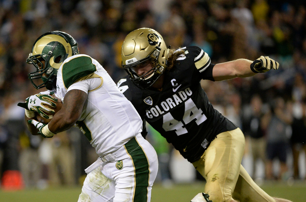 . DENVER, CO. - AUGUST 29:  Colorado State RB, Treyous Jarrells, left, gets past Colorado University ILB, Addison Gillam in the third quarter at the Rocky Mountain Showdown at Sports Authority Field at Mile High Friday evening, August 29, 2014. (Photo By Andy Cross / The Denver Post)