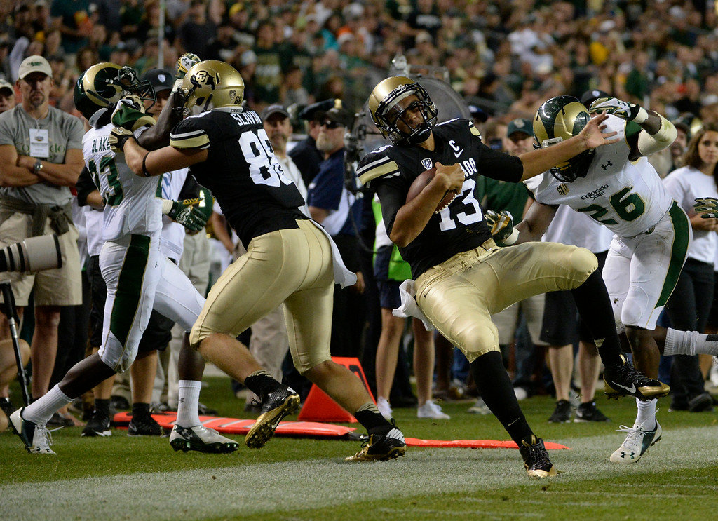 . DENVER, CO. - AUGUST 29: Colorado University QB, Sefo Liufau, , #13, gets pushed out of bounds by Kevin Pierre-Louis, #26, along the CSU sideline in the third quarter at the Rocky Mountain Showdown at Sports Authority Field at Mile High Friday evening, August 29, 2014. (Photo By Andy Cross / The Denver Post)