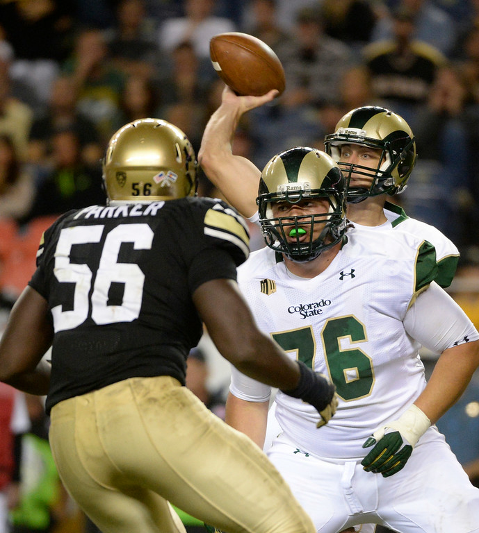 . DENVER, CO. - AUGUST 29: Colorado State QB, Garrett Grayson, passes as offensive lineman, Nick Callender, fends off CU defender, Juda Parker, in the third quarter at the Rocky Mountain Showdown at Sports Authority Field at Mile High Friday evening, August 29, 2014. (Photo By Andy Cross / The Denver Post)