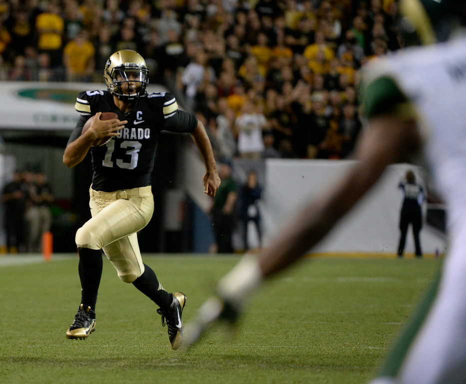 . DENVER, CO. - AUGUST 29: Colorado University QB, Sefo Liufau, left, finds running room against the Colorado State defense in the third quarter at the Rocky Mountain Showdown at Sports Authority Field at Mile High Friday evening, August 29, 2014. (Photo By Andy Cross / The Denver Post)