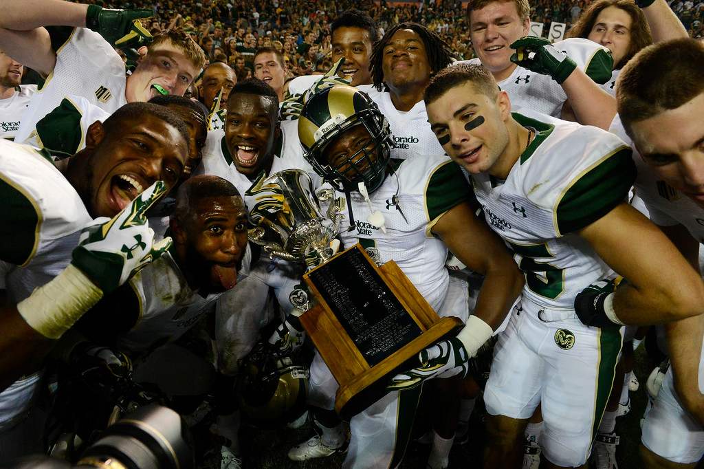 . DENVER, CO. - AUGUST 29:  Colorado State RB, Charles Lovett, center, holds the trophy and celebrates with his teammates after defeating Colorado University 31-17 at the Rocky Mountain Showdown at Sports Authority Field at Mile High Friday evening, August 29, 2014. (Photo By Andy Cross / The Denver Post)