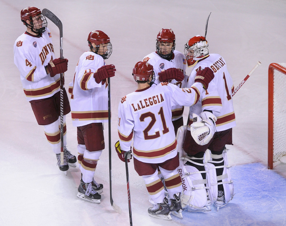 . DENVER, CO. - OCTOBER 11: Teammates skated over to congratulate goalie Sam Brittain after he completed a shutout Friday night. The University of Denver men\'s hockey team defeated Merrimack 1-0 at Magness Arena Friday night, October 11, 2013. Photo By Karl Gehring/The Denver Post
