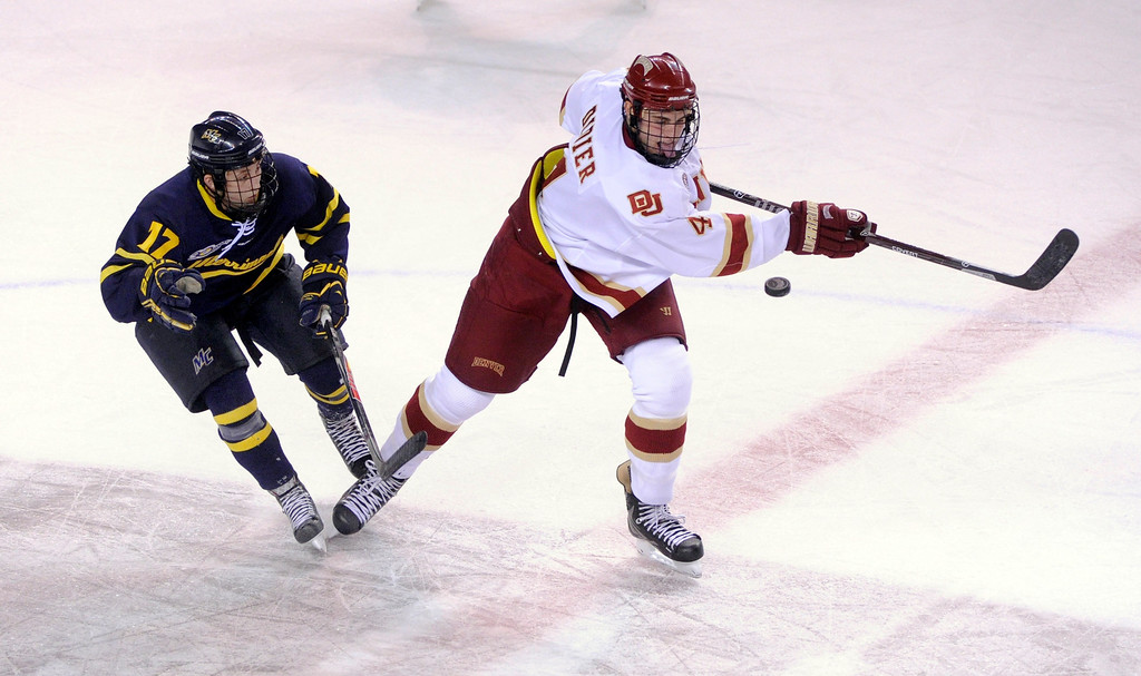 . DENVER, CO. - OCTOBER 11: Denver defenseman Josiah Didier (4) slapped at a puck followed by Merrimack wing Ben Bahe (17) in the first period. The University of Denver men\'s hockey team hosted Merrimack at Magness Arena Friday night, October 11, 2013. Photo By Karl Gehring/The Denver Post