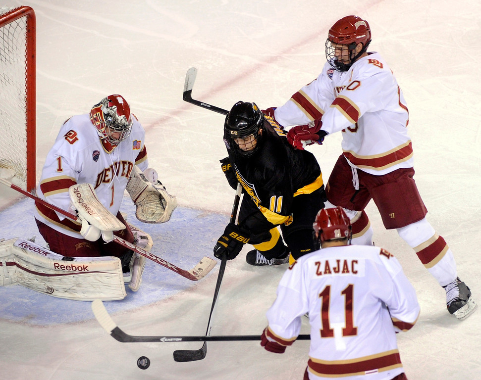 . Denver defenseman David Makowski (10) knocked Tigers wing Hunter Fejes (11) off a rebound in the second period. The University of Denver hockey team hosted Colorado College at Magness Arena Saturday night, November 9, 2013. Photo By Karl Gehring/The Denver Post