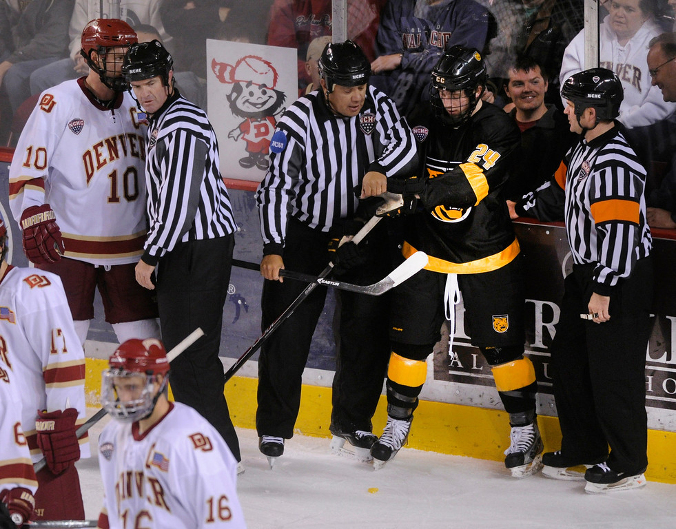 . Officials stepped between Denver defenseman David Makowski (10) and CC wing Jared Hanson (24) in the third period. The University of Denver hockey team defeated Colorado College 2-1 at Magness Arena Saturday night, November 9, 2013. Photo By Karl Gehring/The Denver Post
