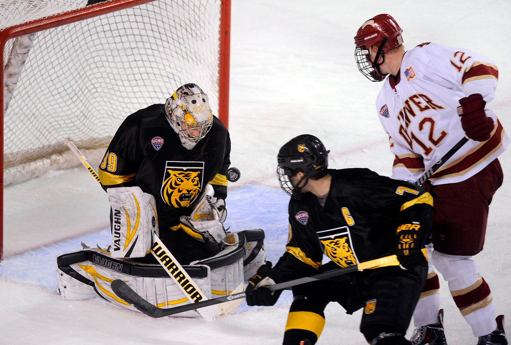. Denver wing Ty Loney (12) looked for a rebound as CC goaltender Josh Thorimbert (39) made a save in the first period. The University of Denver hockey team hosted Colorado College at Magness Arena Saturday night, November 9, 2013. Photo By Karl Gehring/The Denver Post