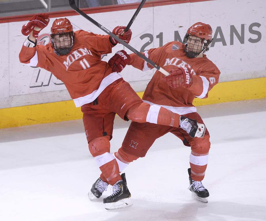 . DENVER, CO - MARCH 7: Teammates Riley Barber, left, and Michael Mooney, right, collided in the second period. The University of Denver hockey team hosted Miami of Ohio at Magness Arena Saturday night, March 8, 2014 in Denver, Colorado. (Photo by Karl Gehring/The Denver Post)
