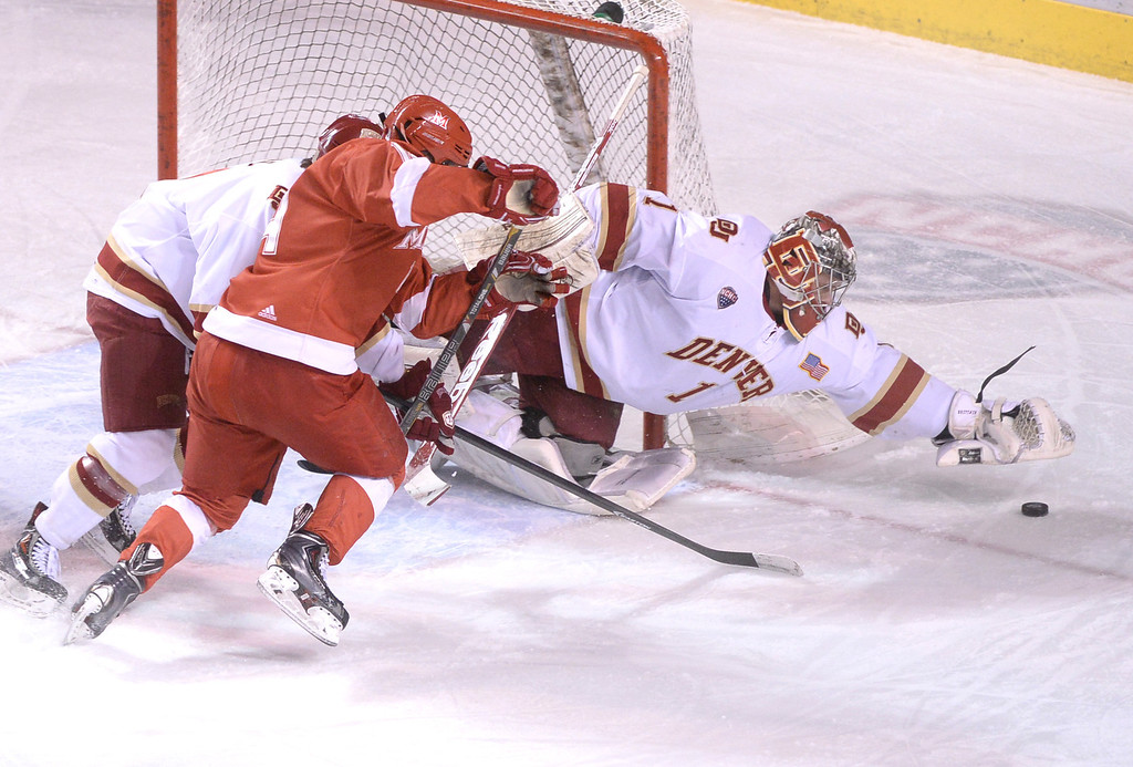 . DENVER, CO - MARCH 7: Denver goalie Sam Brittain pounced on a puck in the first period. The University of Denver hockey team hosted Miami of Ohio at Magness Arena Saturday night, March 8, 2014 in Denver, Colorado. (Photo by Karl Gehring/The Denver Post)