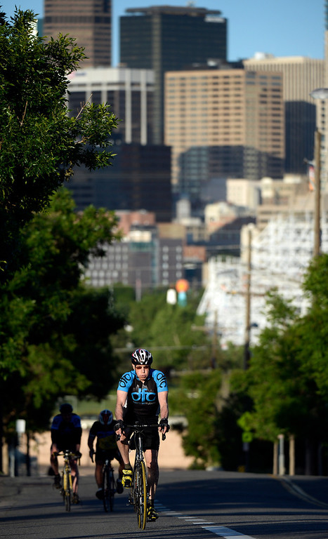 ". DENVER, CO - JUNE 9:  With downtown Denver in the background, instructor Dennis Fitzpatrick rides up the hill on  W. 20th Ave. next to Sports Authority Field as he leads the ""Bicycle Bootcamp\"" on Monday, June 9, 2014. The  bootcamp readies riders for climbing mountain passes this summer.  (Denver Post Photo by Cyrus McCrimmon)"