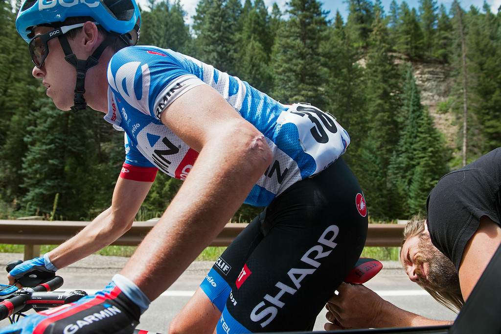. Alex Banyay, right, a Garmin-Sharp bicycle mechanic, leans outside the team car to repair the saddle of Gavin Mannion, left, as he rides in Stage 2 of the USA Pro Challenge from Aspen to Crested Butte on August 19, 2014, near Redstone, Colorado. (Photo by Daniel Petty/The Denver Post)