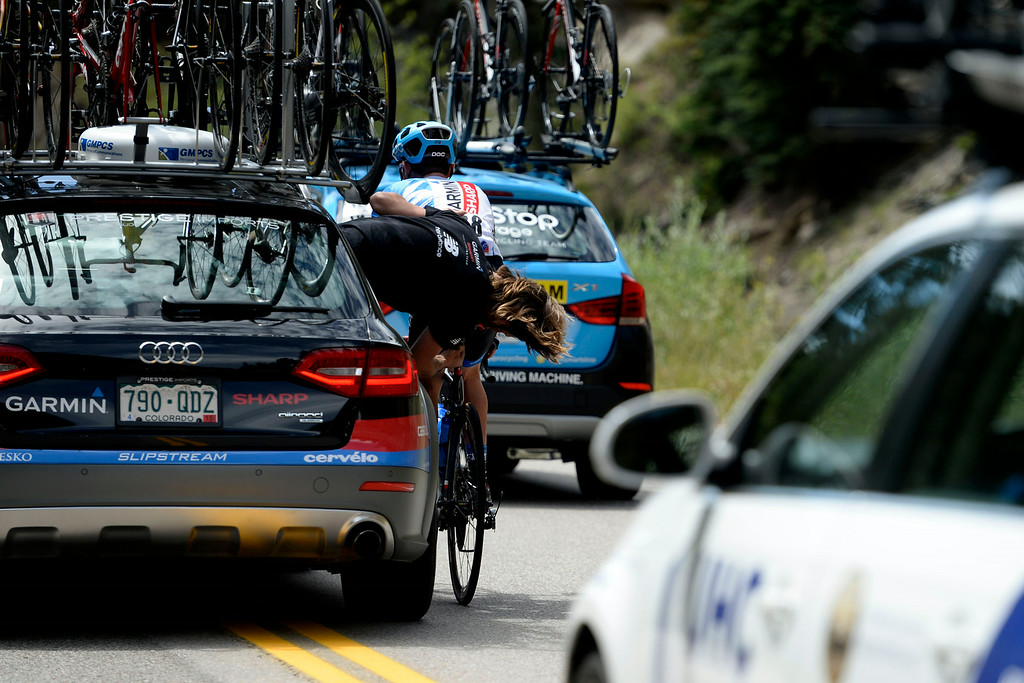 . Alex Banyay, left, a Garmin-Sharp bicycle mechanic, leans outside the team car to repair the saddle of Gavin Mannion, right, as he rides in Stage 2. The USA Pro Challenge stage 2 on Tuesday, August 19, 2014. (Photo by AAron Ontiveroz/The Denver Post)