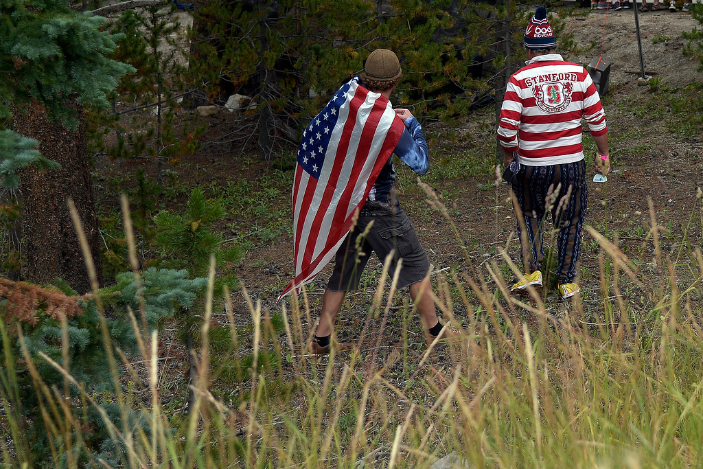 . BRECKENRIDGE, CO - AUGUST 22: Two men support riders from the trees during stage 5. The USA Pro Challenge stage 5 on Friday, August 22, 2014. (Photo by AAron Ontiveroz/The Denver Post)