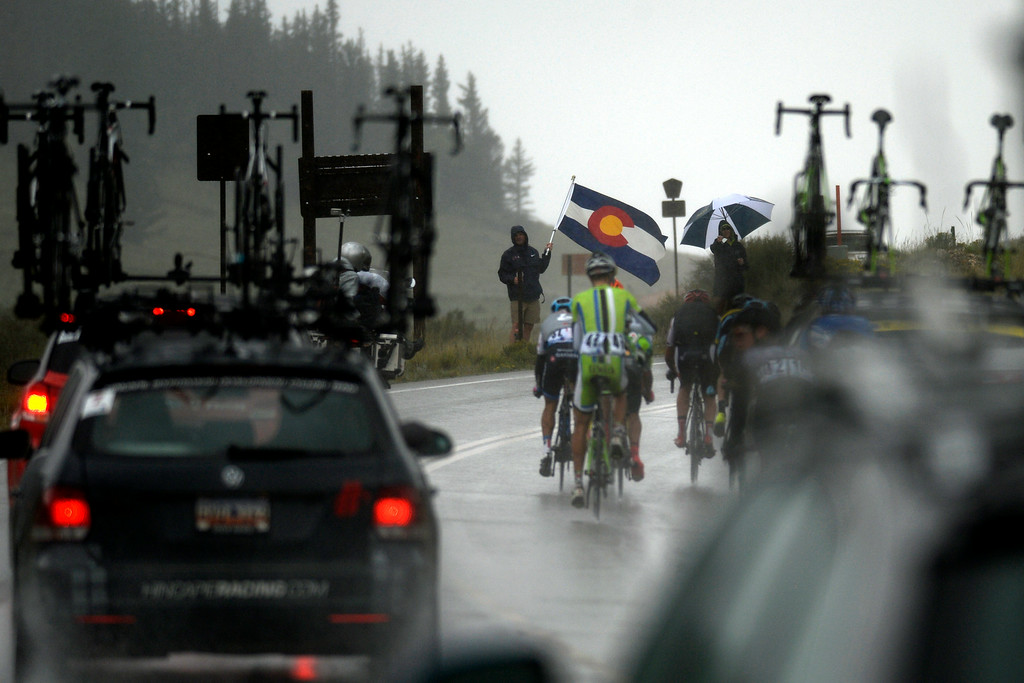 . BRECKENRIDGE, CO - AUGUST 22: A fan braves the weather with a Colorado state flag during stage 5. The USA Pro Challenge stage 5 on Friday, August 22, 2014. (Photo by AAron Ontiveroz/The Denver Post)
