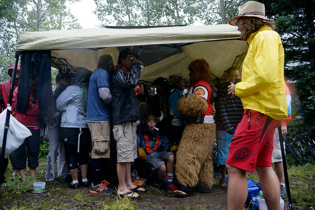 . VAIL, CO - AUGUST 23: Fans take refuge under a small tent as rain falls at the stage 6 finish line. The USA Pro Challenge stage 6 time trial on Saturday, August 23, 2014. (Photo by AAron Ontiveroz/The Denver Post)