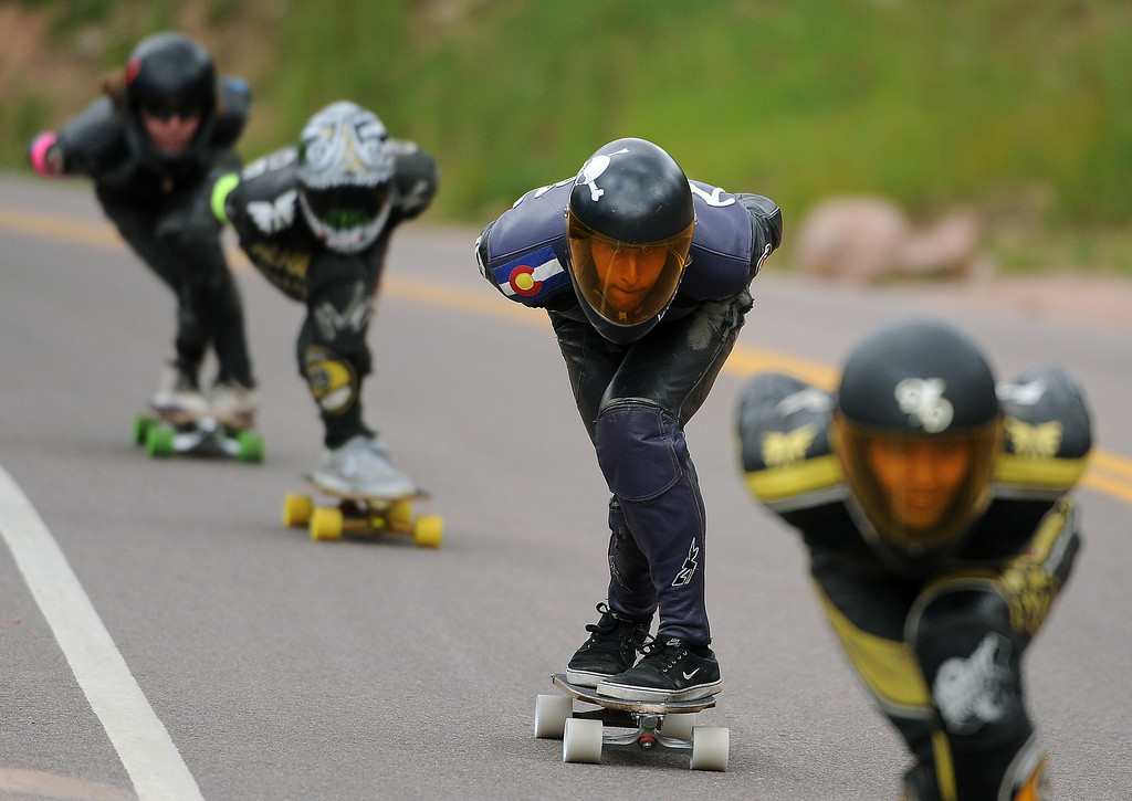 . Elliott Newey of Colorado, second from right, focuses on the road ahead as he races down the course on Pikes Peak outside of Colorado Springs, CO on September 8, 2013 during the International Pikes Peak Downhill Longboarding Competition.  Photo by Helen H. Richardson/The Denver Post