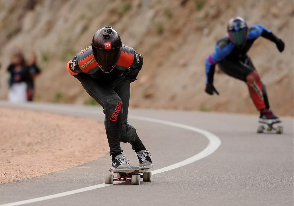 . Garrett Creamer, left, and Gunnar Morin, right,  stay focused on the road ahead of them as they race down the 1.4-mile course on Pikes Peak outside of Colorado Springs on September 8, 2013, during the International Pikes Peak Downhill Longboarding Competition. The course started at 11,446 feet and ended at 10,767 feet giving the riders a 680 foot drop in elevation and grades of 9.2% to 14.15%.  Riders reached speeds of 55 mph.  Ninety-six  competitors started, with 64 qualifying for today\'s race.  Zak Maytum of Boulder, CO won the race.  Photo by Helen H. Richardson/The Denver Post