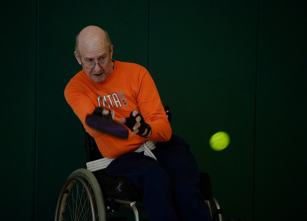 . Pickleball player, Leonard Nelson, returns the wiffle ball at a Pickleball skills and drills session at the Apex Center Tuesday morning, February 11, 2014. Pickleball combines elements of tennis, ping-pong and badminton that is played on a court, half the size of a tennis court. (Photo By Andy Cross / The Denver Post)