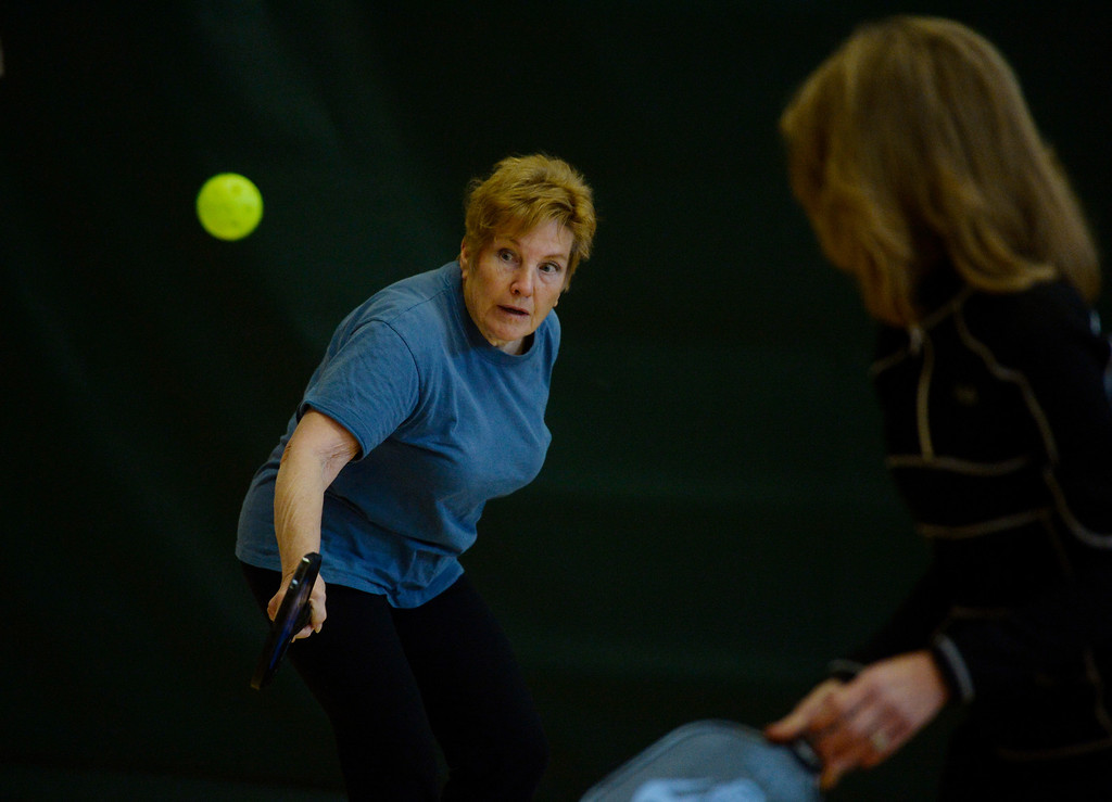 . Pickleball player, Pat Welch, left, fires a shot down court at a Pickleball skills and drills session at the Apex Center Tuesday morning, February 11, 2014. Teammate, Cheryl Mee, right, awaits her next shot. Pickleball combines elements of tennis, ping-pong and badminton that is played on a court, half the size of a tennis court. (Photo By Andy Cross / The Denver Post)