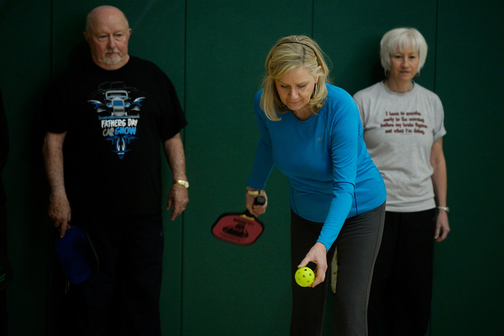 . Pickleball player, Dede Couey, center, serves up the wiffle ball at a Pickleball skills and drills session at the Apex Center Tuesday morning, February 11, 2014. Pickleball players, Don Hagen, left, and Brooks Temple, right, wait their turn in line for the drill. Pickleball combines elements of tennis, ping-pong and badminton that is played on a court, half the size of a tennis court. (Photo By Andy Cross / The Denver Post)