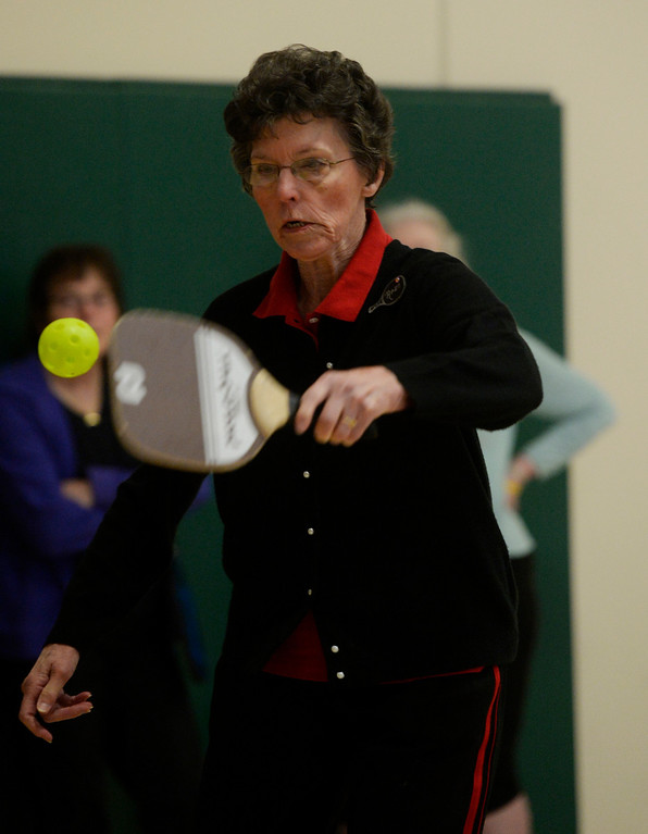 . Pickleball player, Rose Swier, 78, returns a shot at a Pickleball skills and drills session at the Apex Center Tuesday morning, February 11, 2014. Pickleball combines elements of tennis, ping-pong and badminton that is played on a court, half the size of a tennis court. (Photo By Andy Cross / The Denver Post)