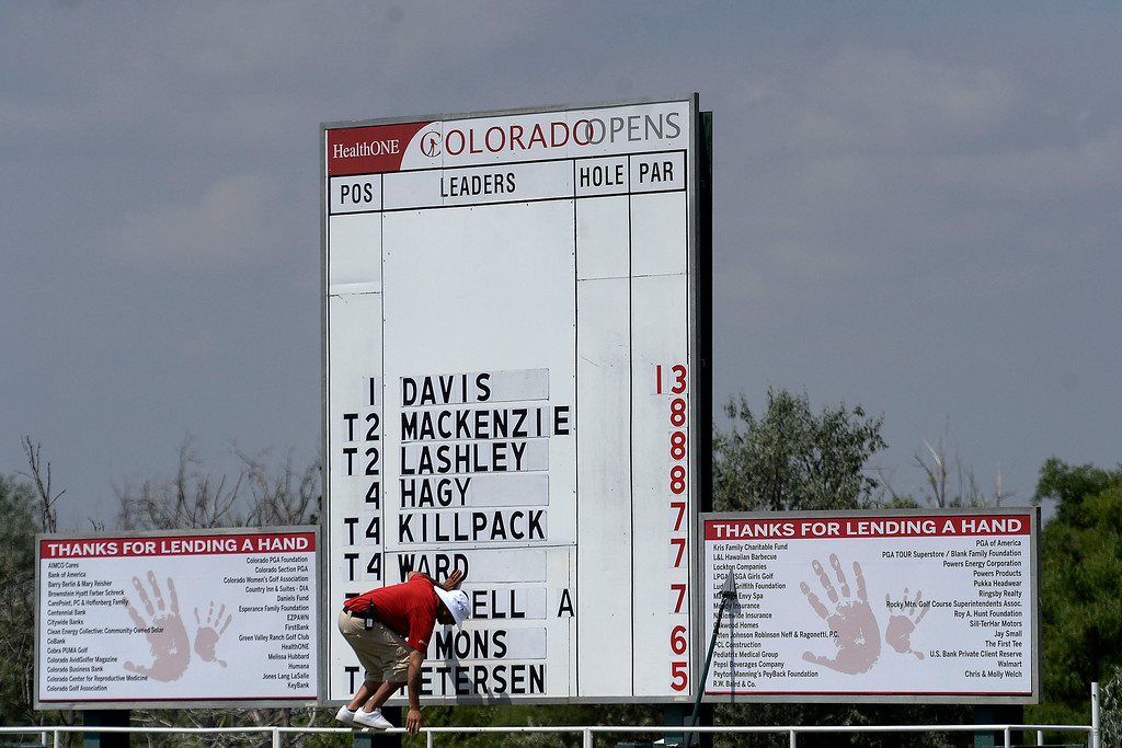 . A score keeper hops down from his perch on the scoreboard during the Colorado Open on Sunday, July 27, 2014. (Photo by AAron Ontiveroz/The Denver Post)