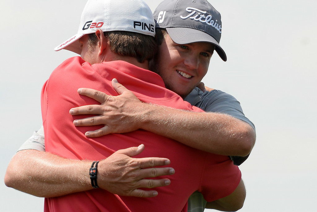 . Champion Ian Davis gets a hug after clinching the title during the Colorado Open at the Green Valley Ranch Golf Club on Sunday, July 27, 2014. (Photo by AAron Ontiveroz/The Denver Post)