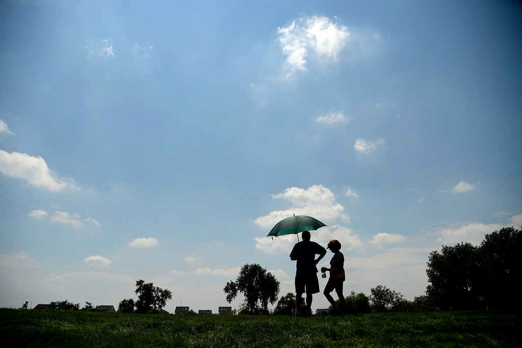 . Pat and Mary Collins shade themselves as they watch the lead group play the back nine during the Colorado Open at the Green Valley Ranch Golf Club on Sunday, July 27, 2014. (Photo by AAron Ontiveroz/The Denver Post)