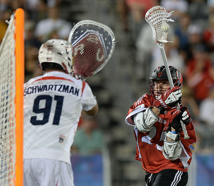 . COMMERCE CITY, CO - JULY 19:  Canada midfielder Jeremy Noble (25) angled to the net defended by US goalie Jesse Sxhwartzman (91) in the second half. Canada defeated the United States 8-5 in the FIL World Lacrosse Championship game Saturday night, July 19, 2014.  Photo by Karl Gehring/The Denver Post