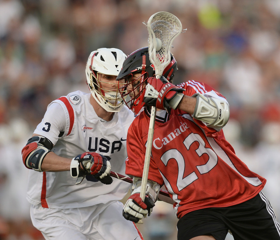 . COMMERCE CITY, CO - JULY 19: Canada attack Adam Jones (23) worked against US midfielder  Mathew Abbott (3) in the first half. The United States faced Canada in the FIL World Lacrosse Championship game Saturday night, July 19, 2014.  Photo by Karl Gehring/The Denver Post